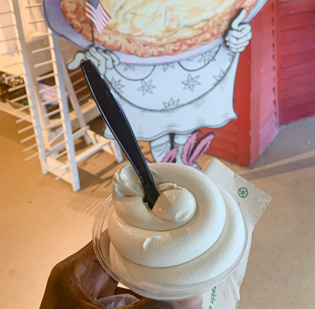 Holding a cup of soft serve maple ice cream in the shop