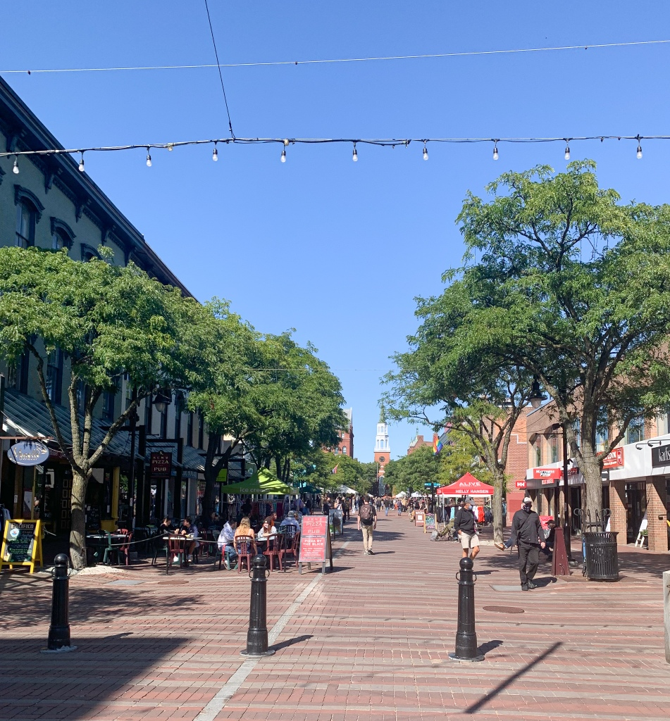 People sitting at outdoor cafes. Trees line the street with a church steeple at the end.