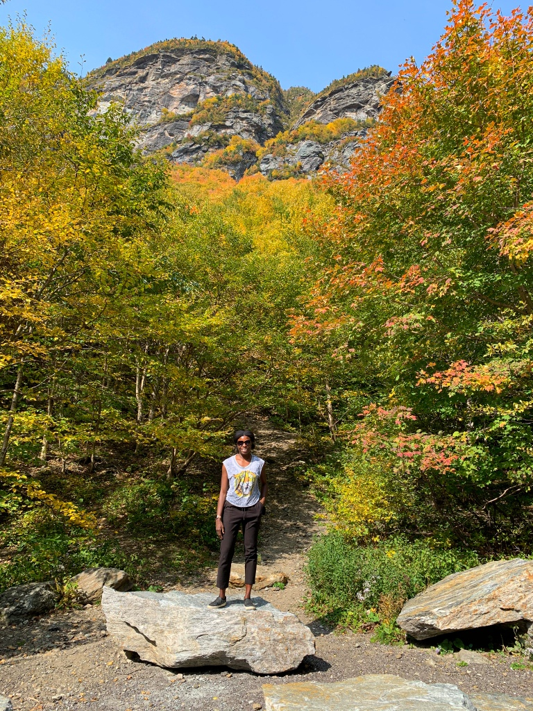 Sho standing on a big rock in front of bright yellow trees along the mountain ridge