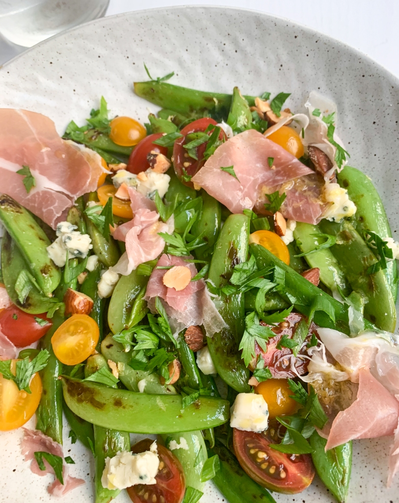 a close-up on the assembled sugar snap salad with ribbons of prosciutto, grape tomatoes, lemon dressing and crumbled blue cheese and chopped almonds.